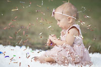 A funny little girl in a bright confetti. Child celebrates one year. Beautiful baby.