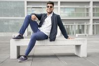 Portrait of young man in stylish sunglasses posing near modern building.