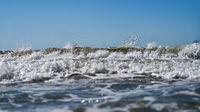 Welle mit Gischt und Spritzern Wasser im Meer vor Himmel