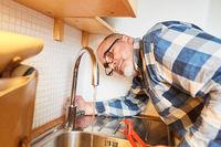 Klempner prüft Mischbatterie am Wasserhahn