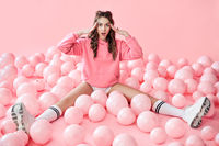 Young trendy surprised woman with pink balloons on pink pastel background