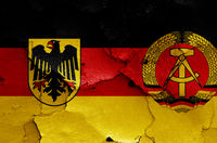 historical flags of West Germany and East Germany painted on cracked wall