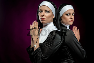 Portrait of two attractive young nuns praying