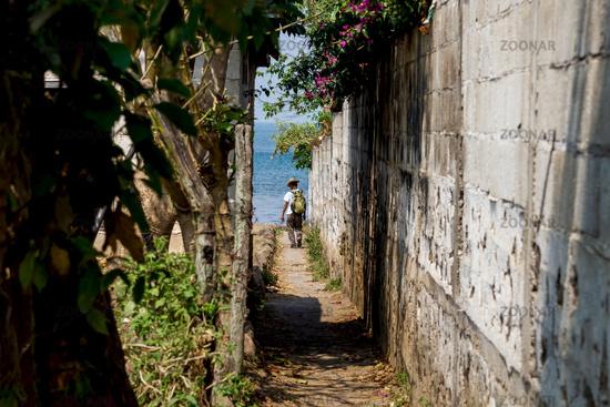 Local man with cowboy hat walking down a small path to the lake Atitlan in San Pedro la Laguna, Guatemala