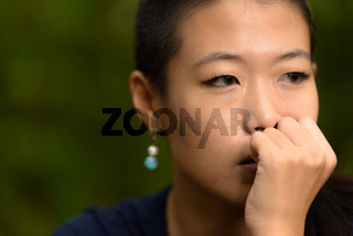Close-up portrait of beautiful rebel Asian woman face thinking outdoors