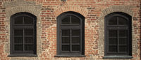 Brick wall of an old building with arched windows.