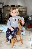 kleines Mädchen sitzt im Wohnzimmer auf einem Kinderstuhl aus Holz