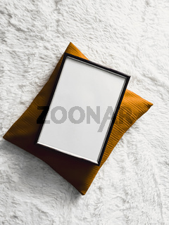 Black thin wooden frame with blank copyspace as poster photo print mockup, golden cushion pillow and fluffy white blanket, flat lay background and art product