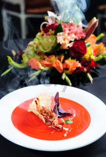 Tomato soup garnished with ham and herbs with alder smoke