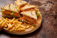Club sandwiches served on a wooden board. With hot French fries