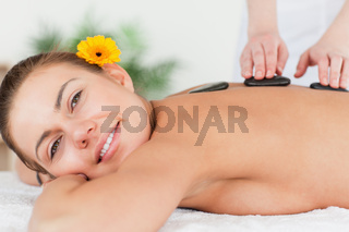 Charming woman having a hot stone massage