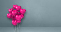 Pink heart shape balloons bunch on a grey wall background. Horizontal banner.