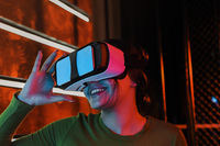 Cheerful woman in VR glasses under neon light