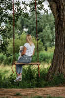 Young woman with a white dog on a tree swing.