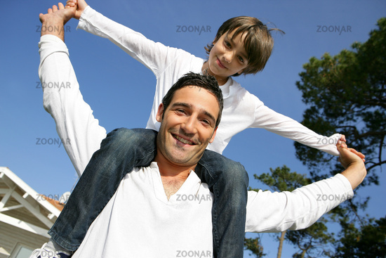 Father carrying his son on his shoulders