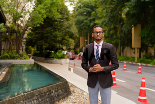 Portrait of handsome young African businessman outdoors in city