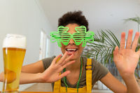 Happy mixed race woman celebrating st patrick's day making video call and waving