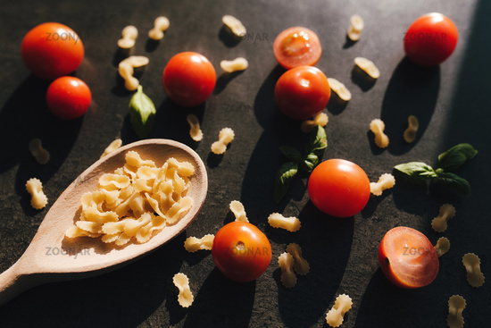 Cherry tomatoes, basil, butterfly vermicelli, wooden spoon, gray background