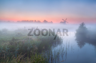 windmill and river with dense fog