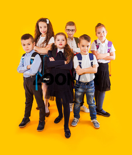 Group of happy kids in uniform with school bags hugging and looking to camera over yellow background