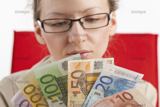 Brillentragende Frau mit Geldfächer im Vordergrund