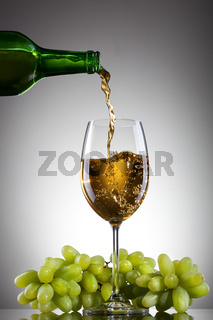 White wine pouring into glass from bottle with green grape
