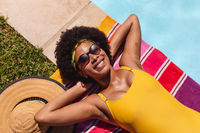 Mixed race woman sunbathing by pool on a sunny day smiling