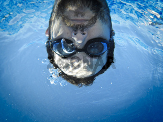 Man face swimming underwater in the pool