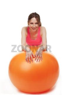 junge frau stützt sich auf orangenem fitness ball