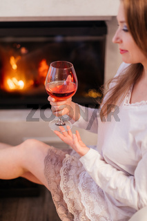 the attractive girl resting by the fireplace with a glass of wine