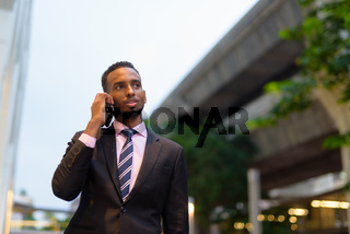 Young African businessman outdoors in city talking on mobile phone