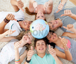 Teenagers on the floor with a terrestrial globe in the center and with thumbs up
