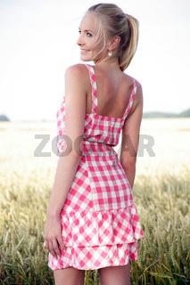 Junge Frau steht vor einem Kornfeld