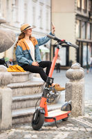 Young woman, sitting on staircase of old historical building in city center, taking picture with her phone. Female traveler exploring Ljubljana's old town on electric scooter. Summer leisure.