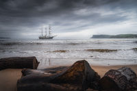 Dramatic storm sky rolling over anchored tall ship near Northern Ireland coast