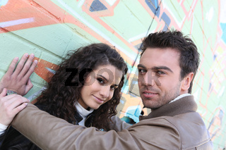 Attractive couple stood in front of graffiti-ed wall
