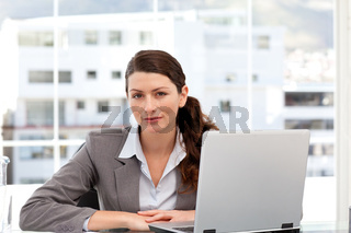 Businesswoman on the computer looking at the camera