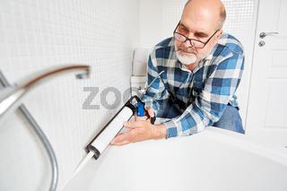 Handwerker beim Fugen abdichten an der Badewanne
