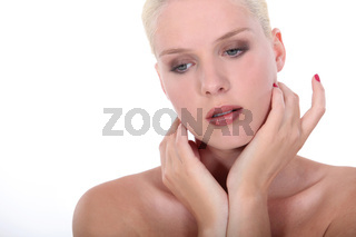 Head and shoulders of a beautiful naked woman wearing makeup