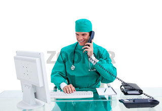 Positive surgeon on phone working at a computer against a white background