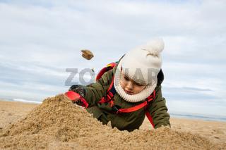 Little boy playing on beach in winter