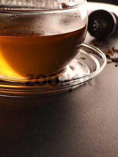 Tea glass with organic chai tea on a stone table, close up