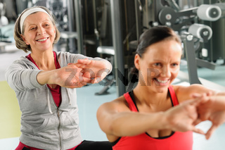 Two women at gym stretch out
