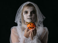 Girl Halloween ghost with candy pumpkin