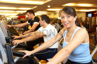 Two man and a woman on exercise bike smiling