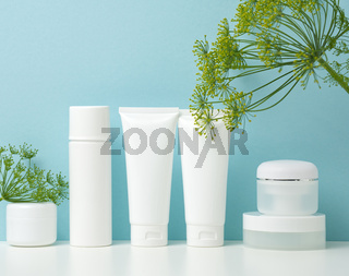 empty white plastic tubes and jars for cosmetics. Packaging for cream, gel, serum, advertising and product promotion