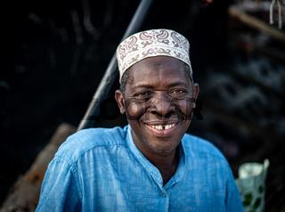 Senior man sitting on coast smiling, High quality photo