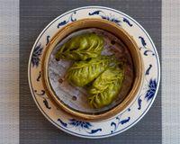 Three Korean green dumplings in a traditional bamboo steamer