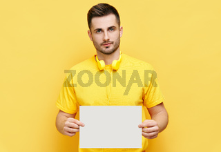 Young caucasian man holding white blank card with copy space for text