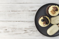 Muffins and cupcakes on tray. Cookie ice creams on a stick. Wooden background
